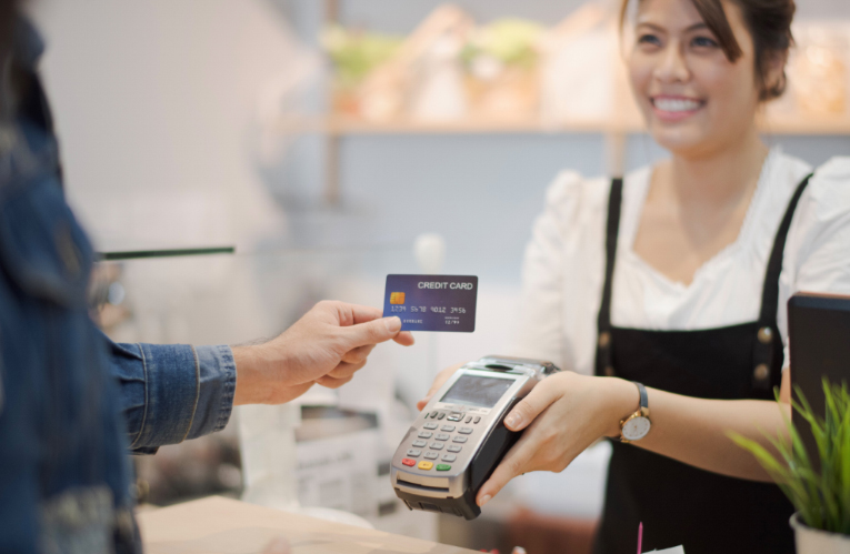 Woman holding credit card terminal to accept credit card